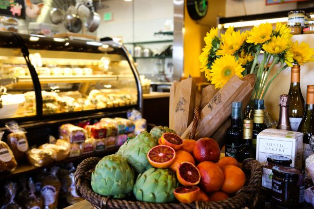 Fruit, wine and flowers on a table with deli counter in the background.