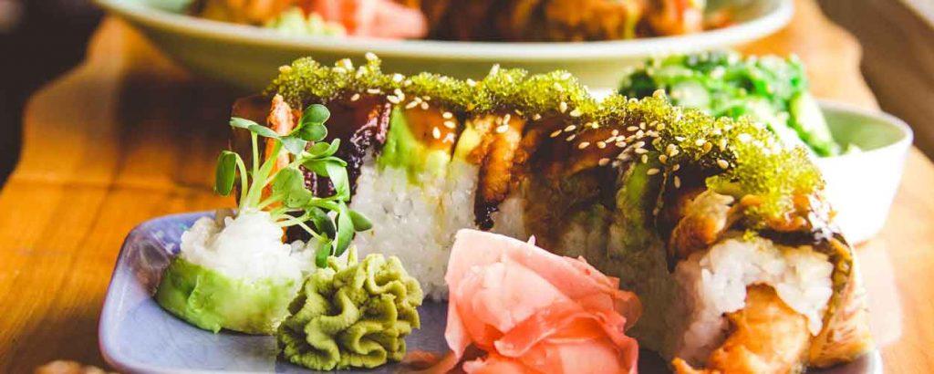 Sushi roll with wasabi and ginger garnish.